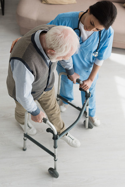 High angle view of doctor helping to senior man walking, recovering after injury