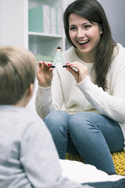 Little boy having private classes with young speech therapist
