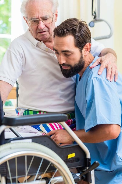 Elderly care nurse helping senior from bed to wheel chair in hospital or nursing home