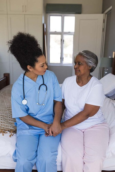 Female doctor comforting senior woman in bedroom at home