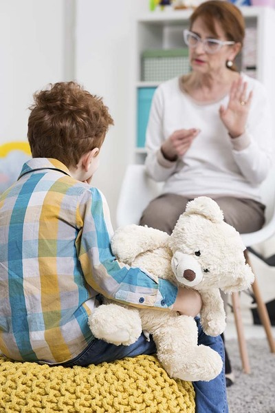 Little boy holding a teddy bear, sitting on a yellow pouffe and being presented sign language by a middle-aged woman in blurry background